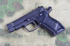 Modern automatic pistol. On camouflage background Stock Photo
