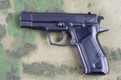 Modern automatic pistol. On camouflage background Stock Photography