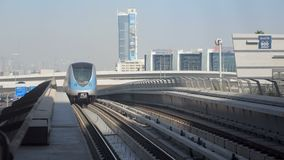 Modern automatical train of aboveground metro is arriving to station in sunny day. View of front stock footage