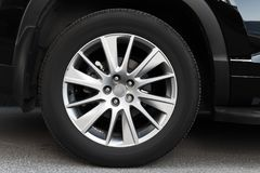 Modern automotive wheel on light alloy disc. Close up photo Stock Photo