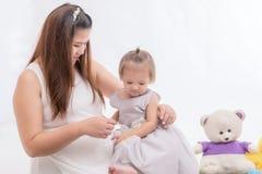 Modern av en ung flicka med ett litet barn som spelar med hennes moder arkivbilder