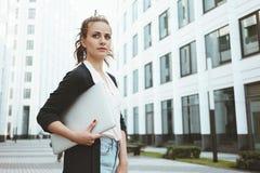 Modern bärbar dator för ung nätt håll för affärskvinna som ser bort, medan stå i stads- gata royaltyfri fotografi