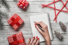 A modern background of a white background carnet background, and a young lady who writes a Christmas message with a white message. A modern background of a royalty free stock image