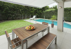 Modern backyard. Modern suburban backyard with table setting and swimming pool Stock Image