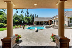 Modern backyard with swimming pool in American mansion. View from the covered porch with columns. Northwest, USA royalty free stock image