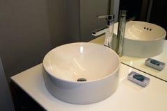 Modern badrumbunkevask, vattenkran och räknare arkivbilder