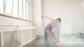 Modern balettdansör i scenisk flödande dräkt som utarbetar på studion stock video