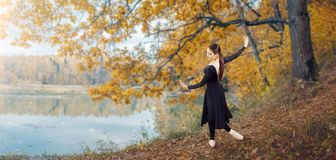 Modern ballet dancer in the autumn park. By the lake. Freedom, harmony and unity with nature royalty free stock images