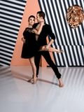Modern ballet dancer couple in black jacket black trousers, black dress performing art jump element with background. Modern ballet dancer couple in black jacket royalty free stock photos