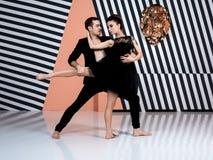 Modern ballet dancer couple in black jacket black trousers, black dress performing art jump element with background. Modern ballet dancer couple in black jacket royalty free stock image