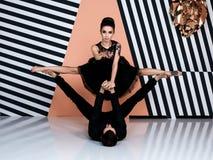 Modern ballet dancer couple in black jacket black trousers, black dress performing art jump element with background. Modern ballet dancer couple in black jacket stock photo