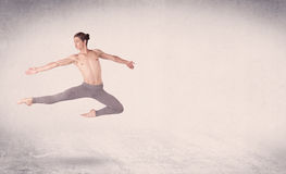 Modern ballet dancer performing art jump with empty background Royalty Free Stock Photo