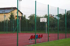 Modern basketball court in the courtyard of primary school. Multifunctional children`s playground with artificial surfaced fenced Royalty Free Stock Images