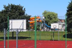 Modern basketball court in the courtyard of primary school. Multifunctional children`s playground with artificial surfaced fenced Royalty Free Stock Photos