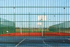 Modern basketball court in the courtyard of primary school. Multifunctional children`s playground with artificial surfaced fenced royalty free stock image