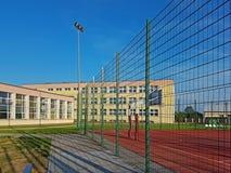 Modern basketdomstol i borggården av grundskola för barn mellan 5 och 11 år Multifunctional lekplats för barn` s med ytbehandlat  Arkivfoto