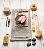 Modern bath and spa setup of female body care products. For sustainable face, dry brushing, nail care and makeup over natural white wooden background, above stock image