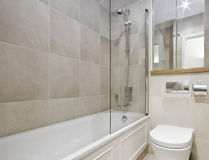 Modern bathroom. With white ceramic appliances and beige floor to ceiling tiles Royalty Free Stock Photography