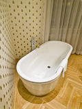 Modern Bathroom. With a bathtub, wooden flooring and wallpaper with bee motif Royalty Free Stock Image