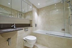 Modern bathroom. With three piece suite and floor to ceiling marble tiles royalty free stock photos
