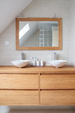 Modern bathroom. Front view of a modern tiled bathroom made in wood with two basins and one mirror Royalty Free Stock Images