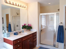 Modern Bathroom. With a wooden vanity, glass door on the shower, and a large mirror with lights above stock image