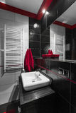 Modern bathroom in black. Image of a functional bathroom with new black tiles, mirror and white basin stock image