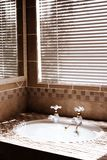 Modern bathroom with blinds. On the window. Shot in the morning, with bright sun coming through the blinds. Artistic grain added to dramatize the interior royalty free stock photos