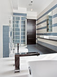 Modern bathroom in blue with shower cubicle. Modern bathroom in blue and gray tones with shower cubicle on wide angle view Royalty Free Stock Photography