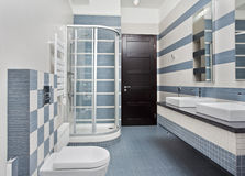 Modern bathroom in blue with shower cubicle. Modern bathroom in blue and gray tones with shower cubicle on wide angle view Stock Photo