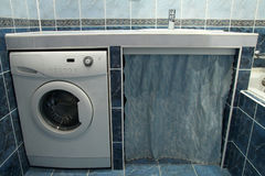 Modern bathroom with blue tiles  and washing machine Royalty Free Stock Photography