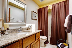 Modern bathroom cabinet with granite top. Brown curtains decorate the room. Modern bathroom cabinet with granite top and mirror. Brown curtains decorate the room royalty free stock photos