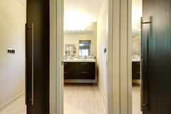 Modern bathroom with closet doors and hallway with mirrors. Stock Image