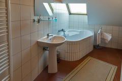 Modern bathroom with corner bath, washbasin and window. Modern white little bathroom with corner bath, washbasin, mirror and window. Banska Stiavnica, Slovakia Royalty Free Stock Photos