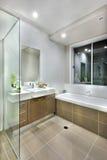 Modern bathroom with dark color floor tiles with lights on Stock Photos