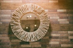 Modern bathroom decor on Wooden wall. With a round mirror over with a border made of twigs stock photos