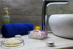 Modern bathroom design with white washbasin and metal crane and decoration. Blue towel and candles and cosmetics against grey wall. Spa table in relaxation Royalty Free Stock Photography