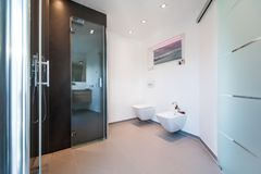 Modern bathroom with glass doors royalty free stock image