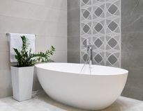 Modern bathroom interior design with white stone bathtub, grey tiles wall, ceramic flowerpot with green plant and hanger with. Towel stock photos