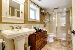 Modern bathroom interior with glass door shower. Modern bathroom interior with wooden cabinet, glass door shower and washbasin stand royalty free stock photo