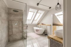 Modern bathroom interior with minimalistic shower. And lighting, white toilet, sink, bathtub and roofwindows