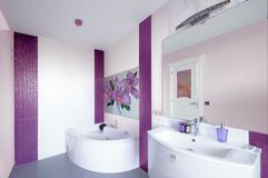 Modern Bathroom interior with a mosaic panel. White bathtub agai. Nst violet and white wall stock images