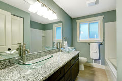 Modern bathroom interior in soft aqua color. Modern bathroom interior with window. View of wooden vanity cabinet with granite counter top and glass vessel sinks Stock Images