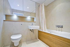 Modern bathroom with large bath tub in beige. Modern bathroom with large bath tub, ceramic wash basin and natural stone tiled walls Royalty Free Stock Photos