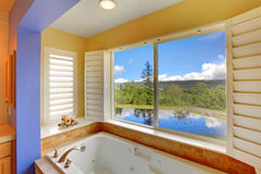 Modern bathroom with large tub and lake view. Royalty Free Stock Photos