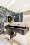 Modern bathroom with mosaic tiles. Modern bathroom with gleaming mosaic tiles and a large mirror Stock Photos
