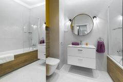 Modern bathroom with oval mirror. In stylish apartment Stock Photography
