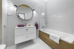 Modern bathroom with oval mirror. In stylish apartment Stock Photo