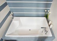 Modern bathroom with rectangular bath tub. Modern bathroom in blue and gray tones with rectangular bath tub Stock Photos
