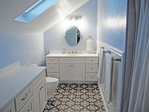 Modern Bathroom Remodel. A bathroom redo in a space with a slanted roof featuring dramatic cement tile Stock Image